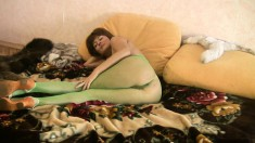 Naughty babe in green pantyhose Helen displays her curves on the bed
