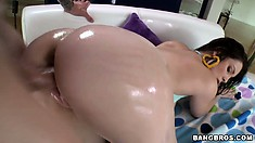 Oiled up again, he fingers her ass while banging her cunt and drops a load