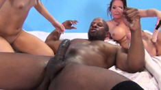 Two alluring babes take turns impaling themselves on a big black pole